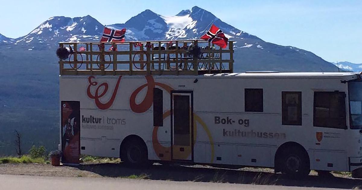 Bok- og kulturbussen pyntet med flagg foran flotte fjell under Arctic race